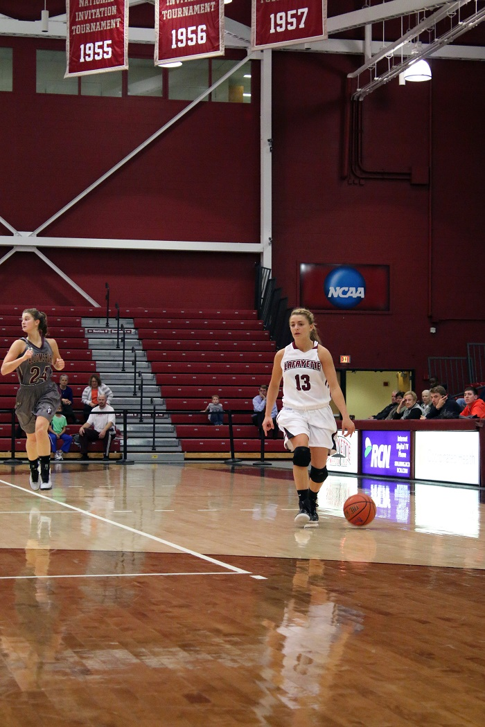 Junior Jamie O'Hare brings the ball up past midcourt at home. She will split time at point guard this season with senior Maddie Pea- body.
