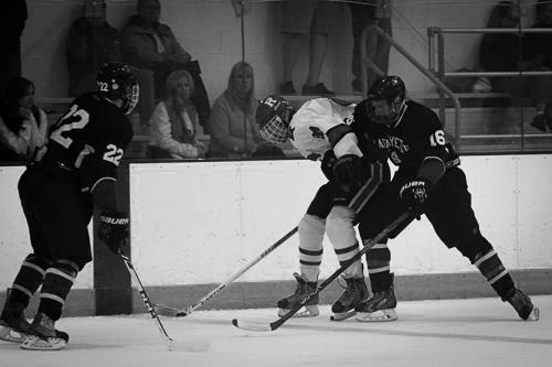 Sophomore Sam Komrower battles for the puck against a defender next to the boards. [Photo Courtesy of Facebook ]