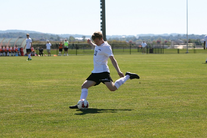 Senior Tom McCutcheon drives the ball downfield to teammates at Metzgar Fields.