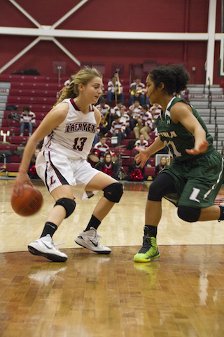 Junior Jamie O'Hare dribbles around her back against a Loyola defender. [Photo By Hana Isihara '17]