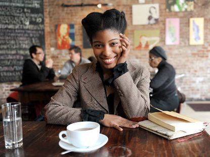 Sharifa Rhodes-Pitts sitting at a coffee table