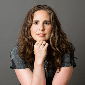Lauren Klein holding her chin up with her hand against a gray background.