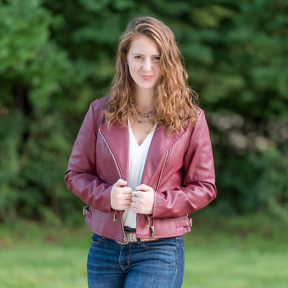 Caroline standing in a grassy field with a jacket on.